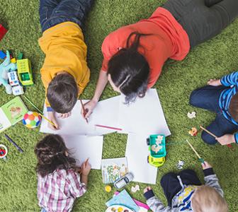Enfants allongés sur herbe dessinant